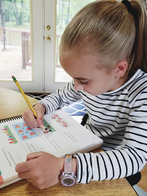 Young girl in blue striped shirt writing with a pencil in an Apologia Math workbook