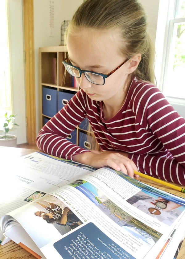 Young girl reading a homeschool earth science textbook at a table