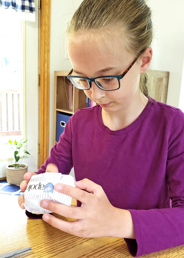 Girl with glasses completing a hands-on science activity
