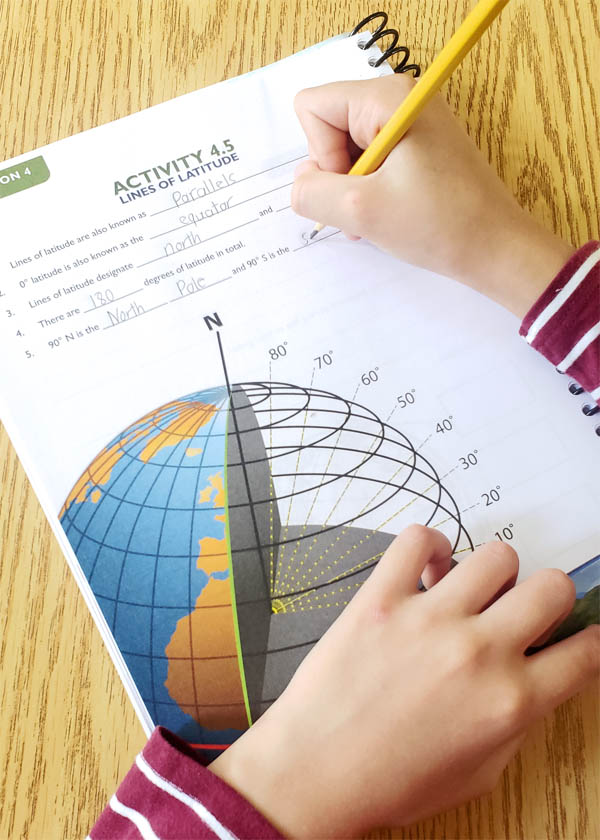Child's hand writing in a colorful science notebooking journal