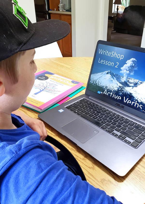 Teen boy watching middle school writing video on laptop