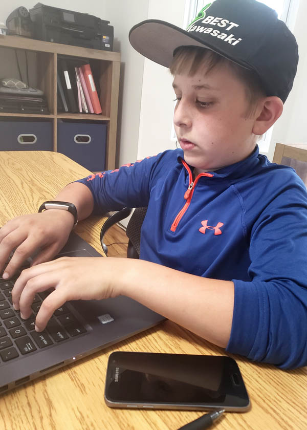 Teen boy in blue shirt and ball cap typing on laptop