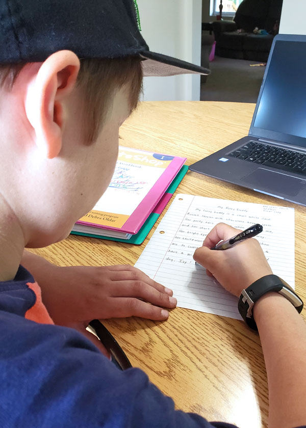 Middle school boy writing on lined paper with black pen