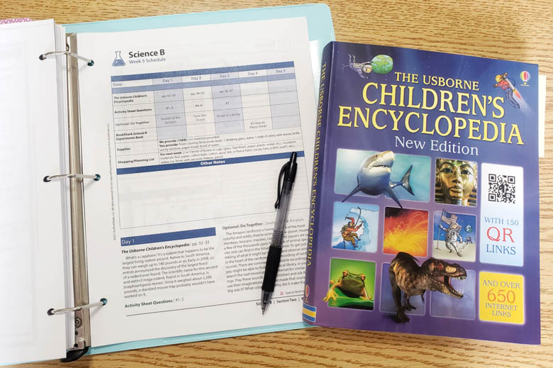 Aqua binder opened to instructor's guide, with a black pen and a children's science book