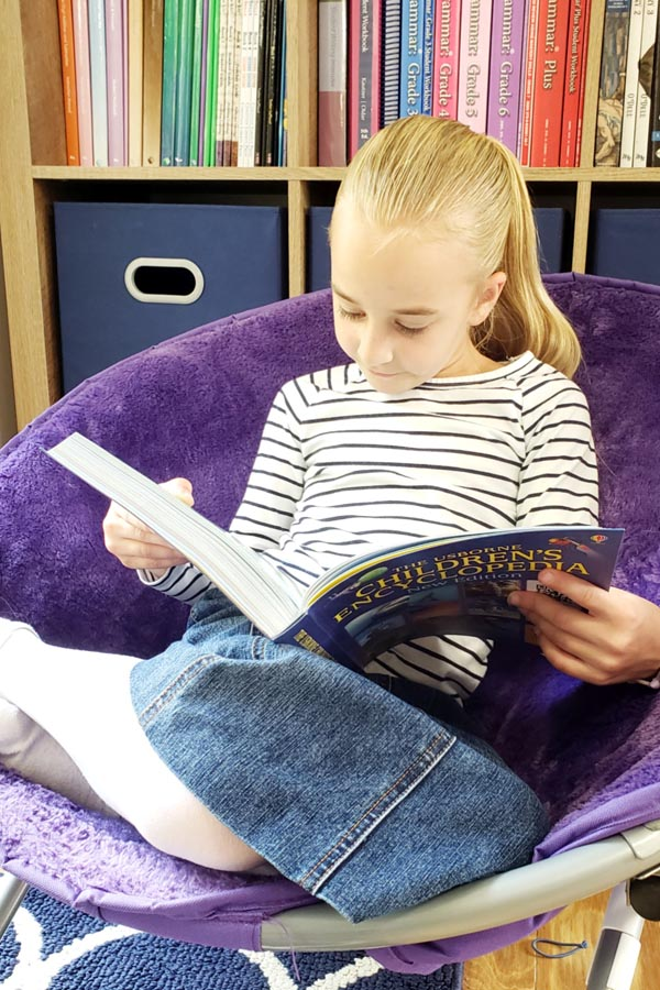 Young girl sitting in purple plush chair reading a living science book