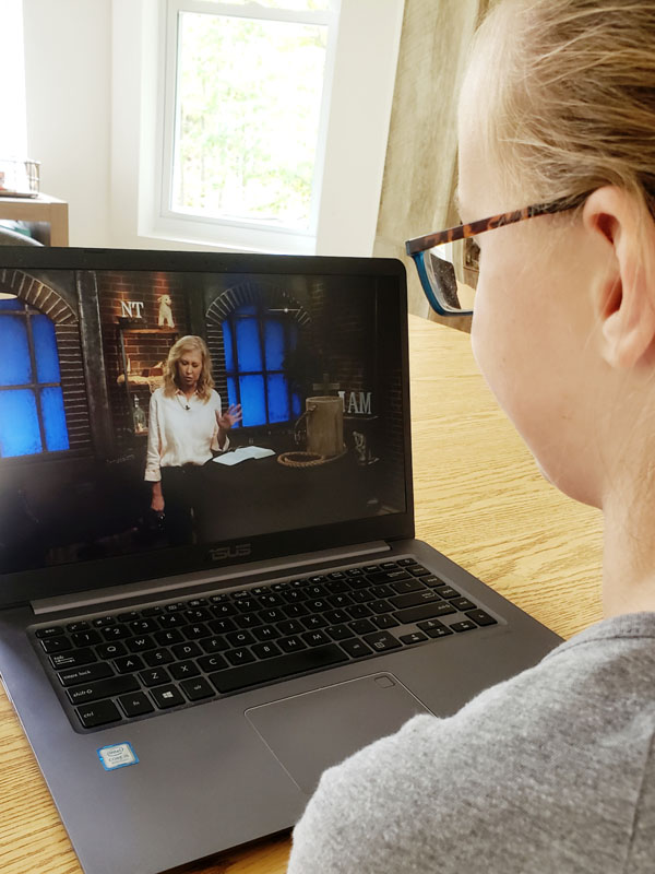 Young girl in glasses watching lesson on laptop computer