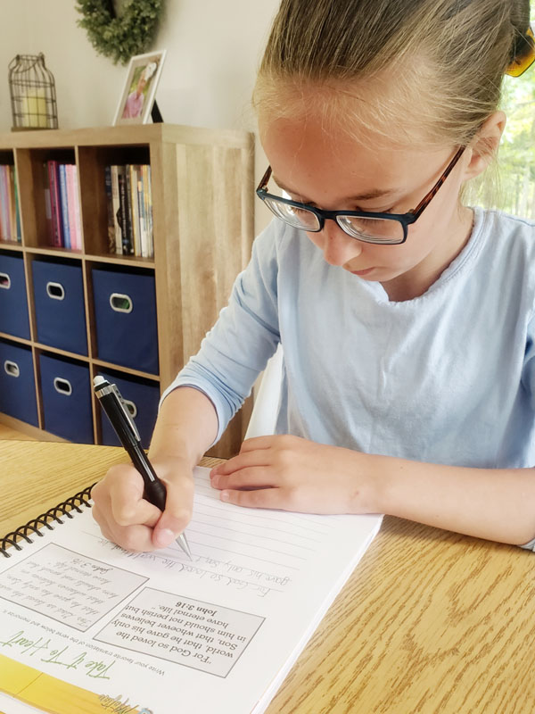 Middle school girl in blue shirt writing in Bible journal