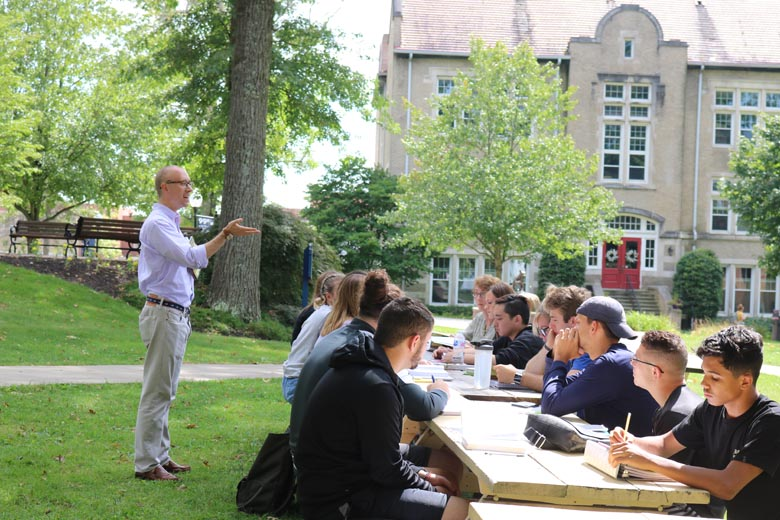 Thiel College students sitting outside at picnic table during a class