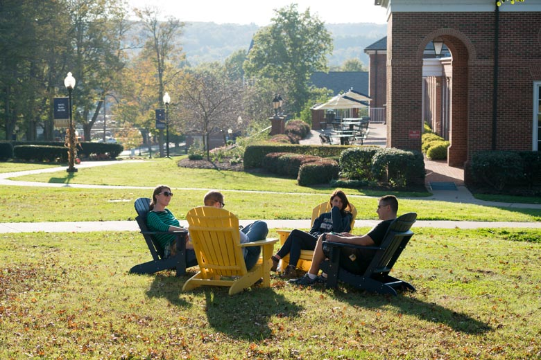 Thiel College students sitting on chairs on the campus lawn on a fall day